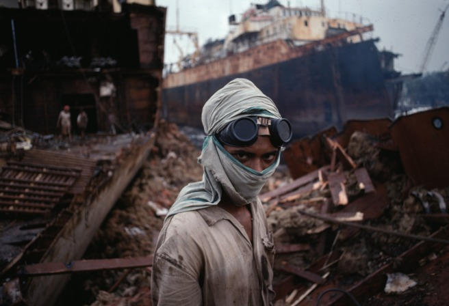 Goggles and scarf shield this worker from the choking dust and smoke of the ship breaking yard.  Old ships are brought from all over the world to be cut up for scrap metal.  National Geographic:  John McCarry (March 1995)  Bombay: India's Capital of Hope, National Geographic. (vol.187 (3)) pp.  42-67  From the tangle of deconstruction in the shipbreaking yard of Bombay, a young welder stepped forward in 1994 to engage the camera. His eyes, redoubled by the goggles on his forehead, draws our gaze away from the ship's empty hold and we wonder about this young man, whose face we cannot read fully, whose head is protected only by the cloth that covers his mouth. The promise of our gaze meeting, through a photograph, the look of another across time and vastly different spaces is one of the signature strengths of McCurry's art. Bannon, Anthony. (2005). Steve McCurry. New York: Phaidon Press Inc., 27.